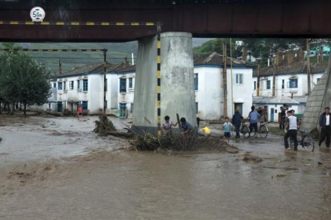 Residents attempt to clear flood debris from under a bridge in the city of Rajin